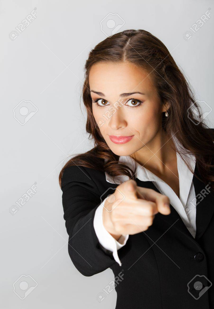 Portrait of young serious business woman pointing finger at viewer, over grey background Stock Photo - 10549096