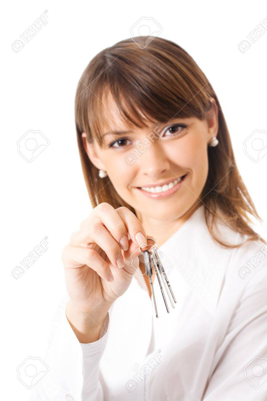 Young happy smiling business woman or real estate agent showing keys from new house, isolated on white background. Focus on keys. Stock Photo - 10850565