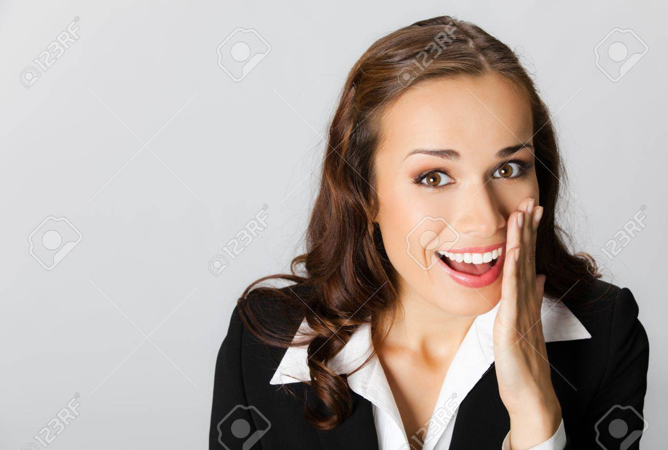 Portrait of happy smiling young business woman covering with hand her mouth, over grey background Stock Photo - 11292290