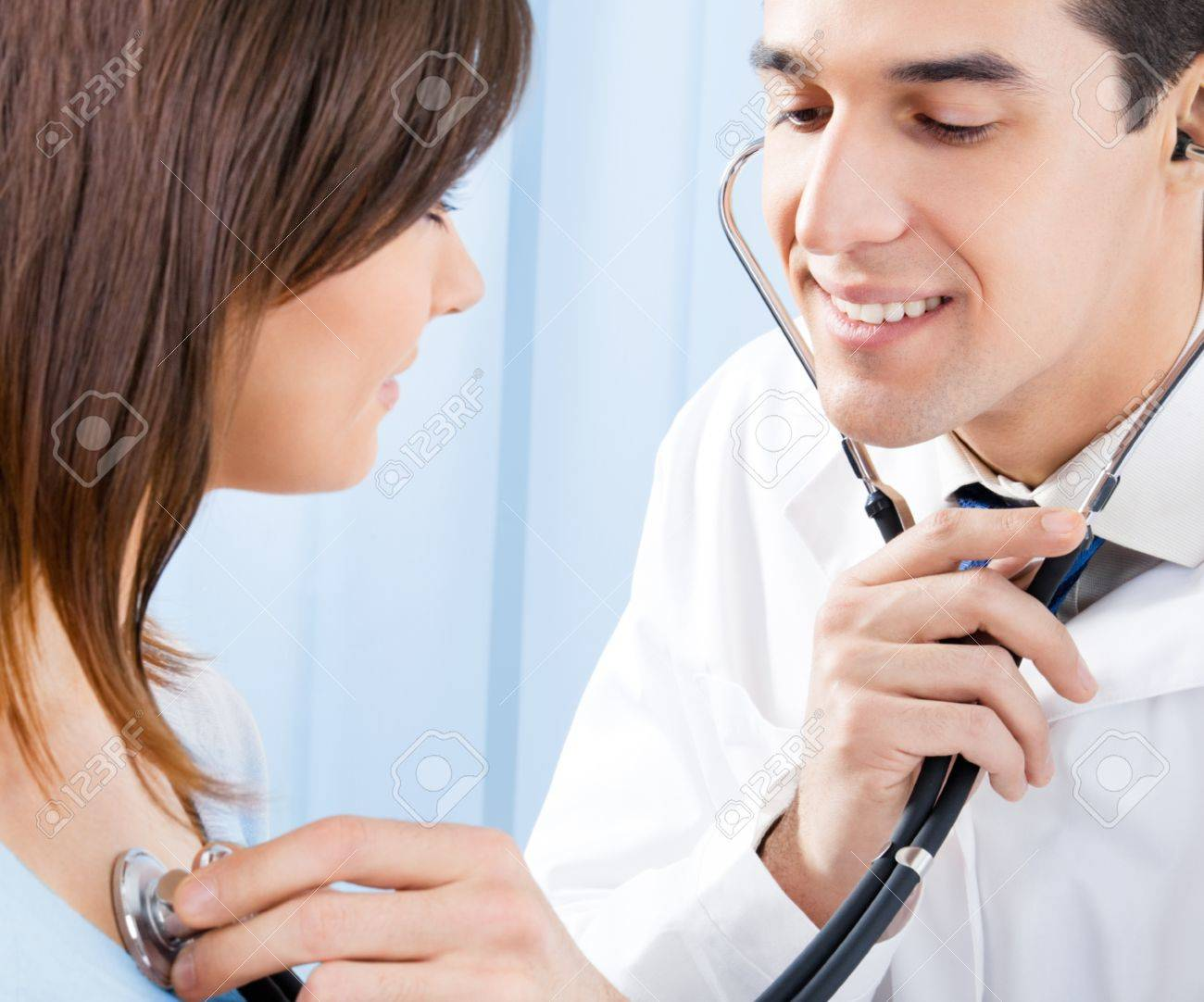 Happy smiling doctor with stethoscope and female patient at office Stock Photo - 12074553