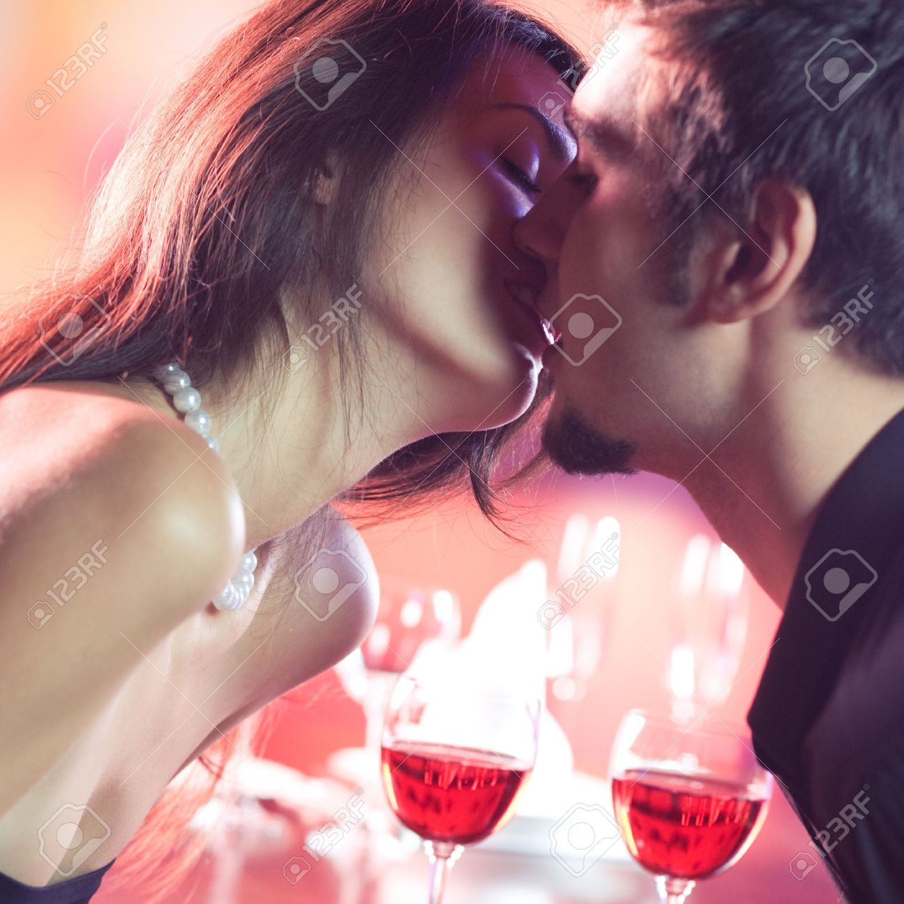 Young happy amorous couple kissing on romantic date, at restaurant Stock Photo - 14158619