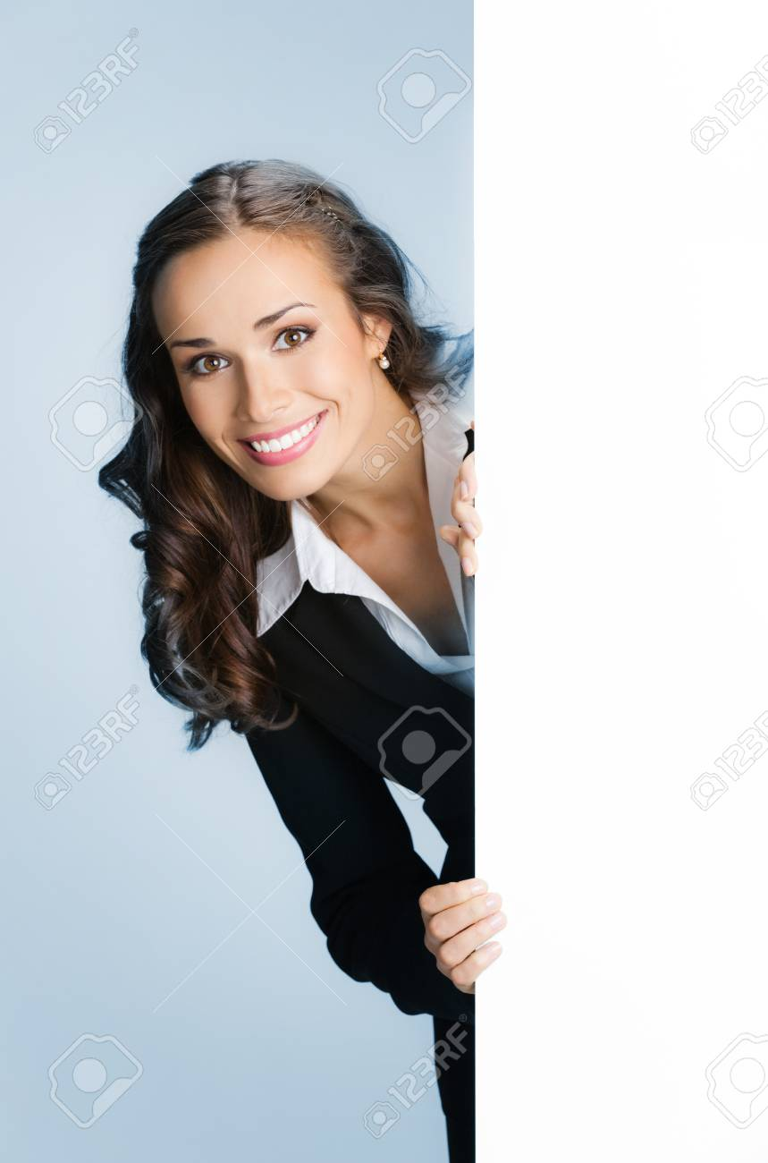 Happy smiling young business woman showing blank signboard, over blue background Stock Photo - 15243050