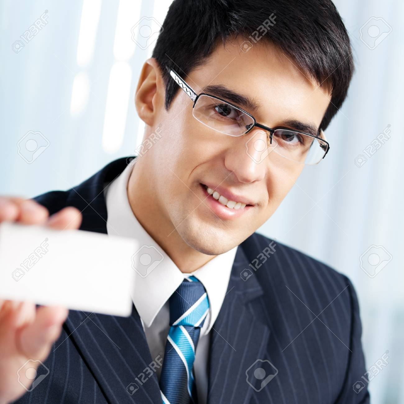 Smiling businessman giving business card, at office Stock Photo - 17154621
