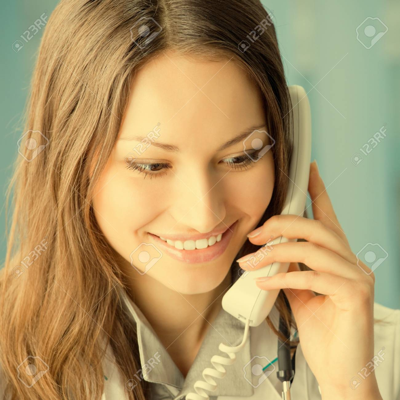 Portrait of happy smiling cheerful young female doctor on phone, at office Stock Photo - 29750463
