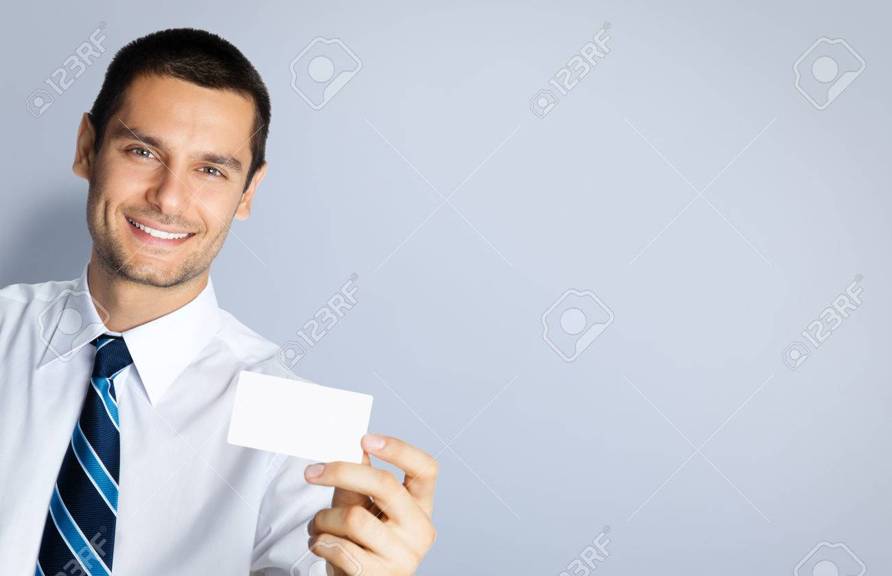 Portrait of smiling businessman showing blank business or plastic credit card, against grey background. Copyspace blank area for slogan or text. Business and success concept. - 41221597