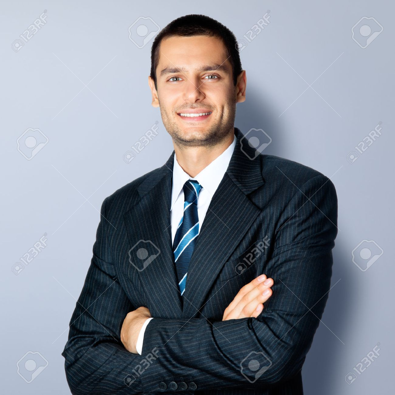 Portrait of happy smiling businessman in crossed arms pose, in black confident suit, against grey background. Caucasian male model at studio shot. Business and success concept. - 41221598