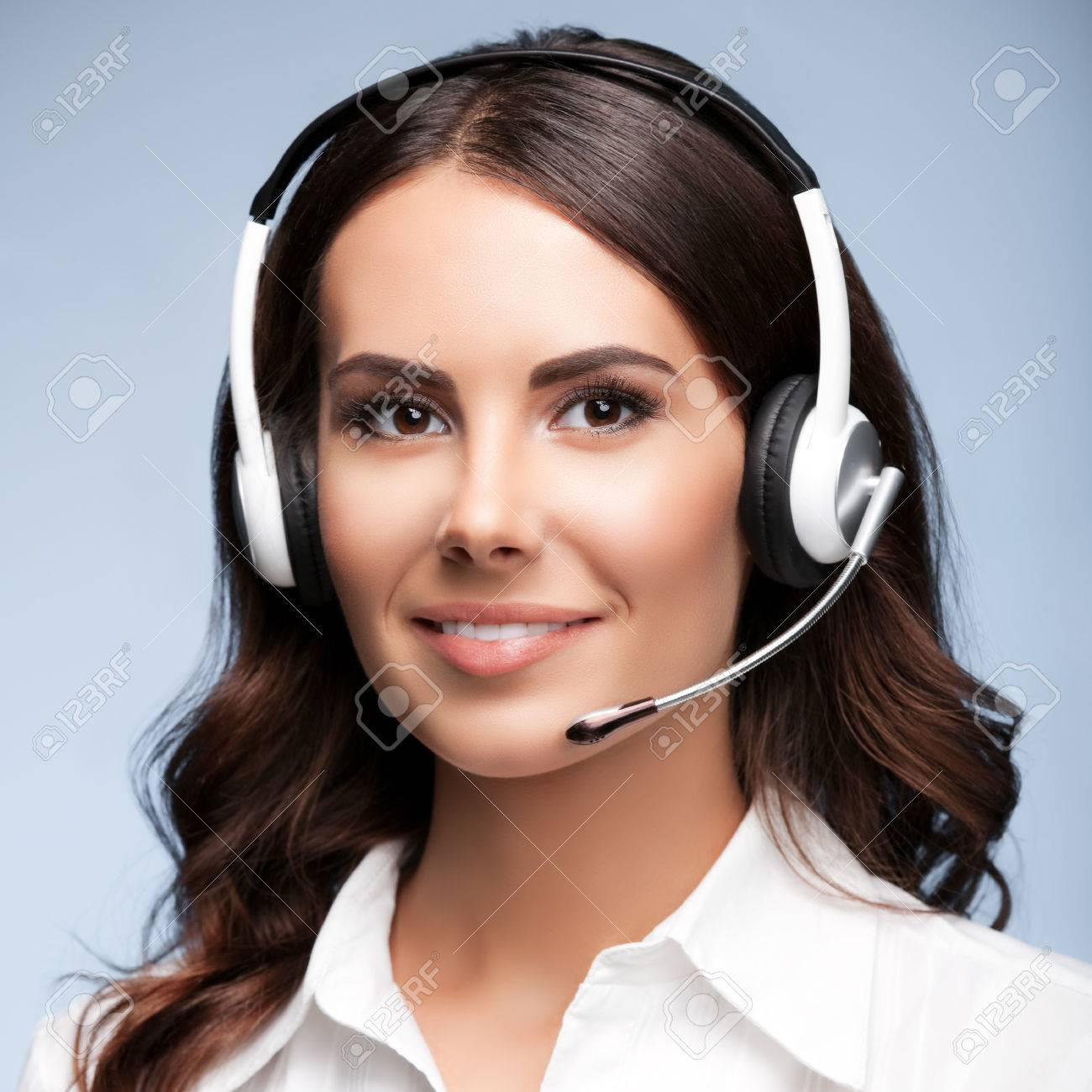 Female customer support phone operator in headset, against grey background. Consulting and assistance service call center. - 41556390