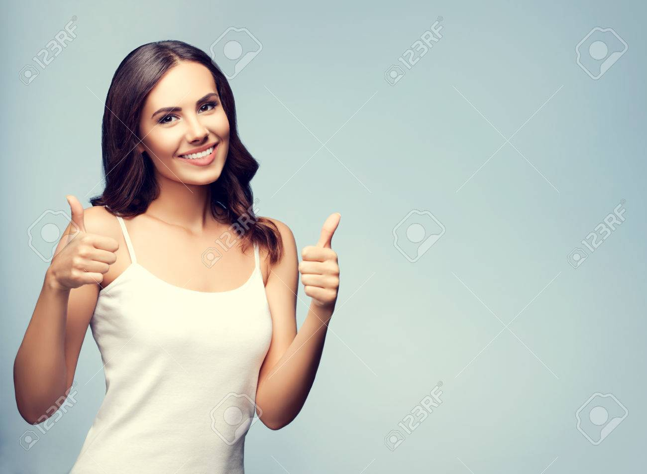 Portrait of beautiful cheerful smiling young woman showing thumb up gesture, with blank copyspace area for text or slogan - 41556468