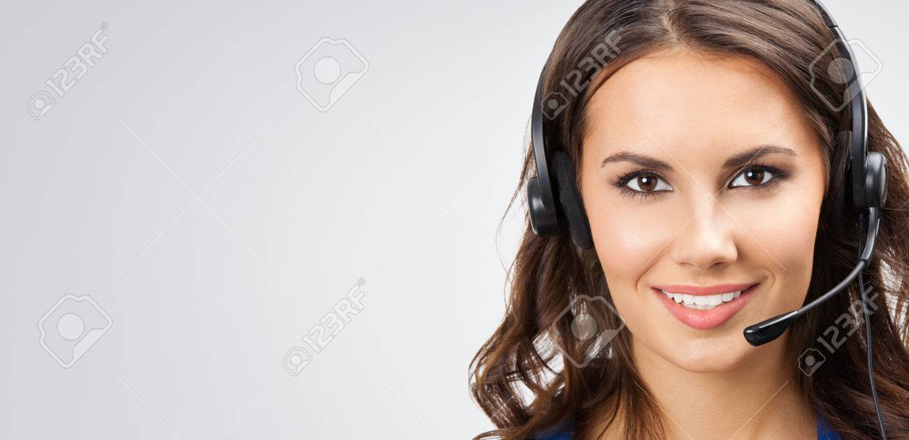 Portrait of happy smiling young support phone operator or businesswomen in headset, with blank copyspace area for slogan or text, posing at studio against grey background Banque d'images - 41556507