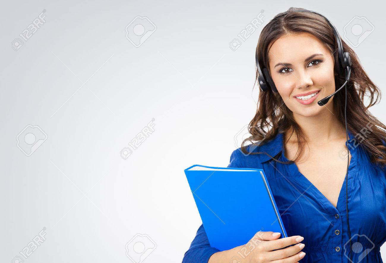 Portrait of happy smiling cheerful beautiful young support phone operator in headset with blue folder, with blank copyspace area for slogan or text, posing at studio against grey background - 41556508