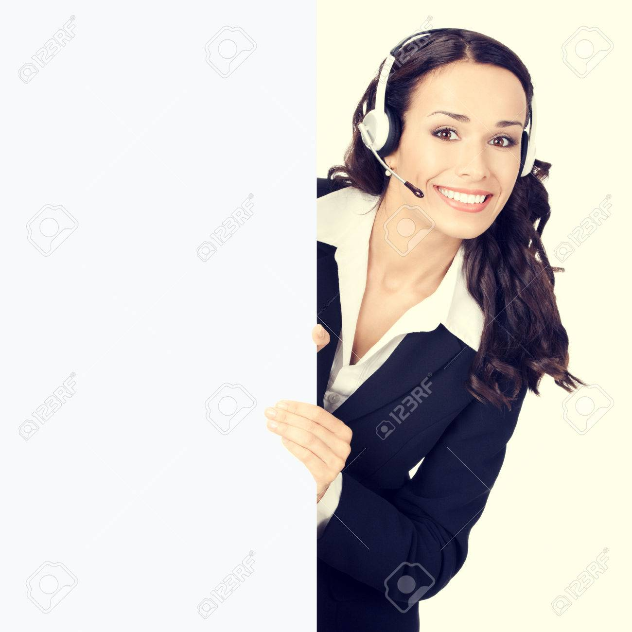 Cheerful young customer support phone operator or businesswoman in headset showing blank signboard Banque d'images - 42155868