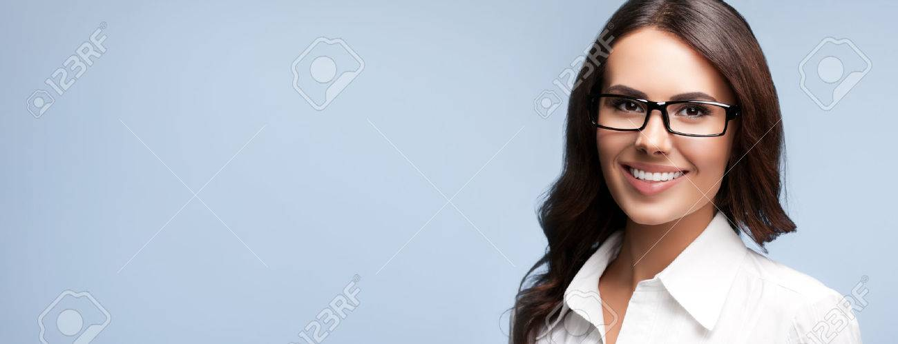 Portrait of happy smiling brunette businesswoman in glasses, over grey background - 42486279