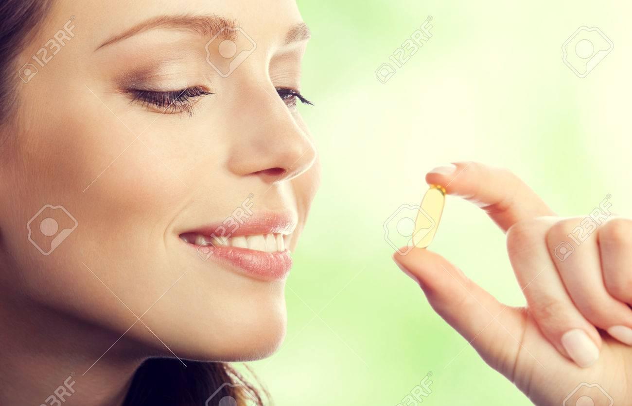 Jeune souriant belle femme brune avec oméga 3 capsules d'huile de poisson, en plein air Banque d'images - 43738034