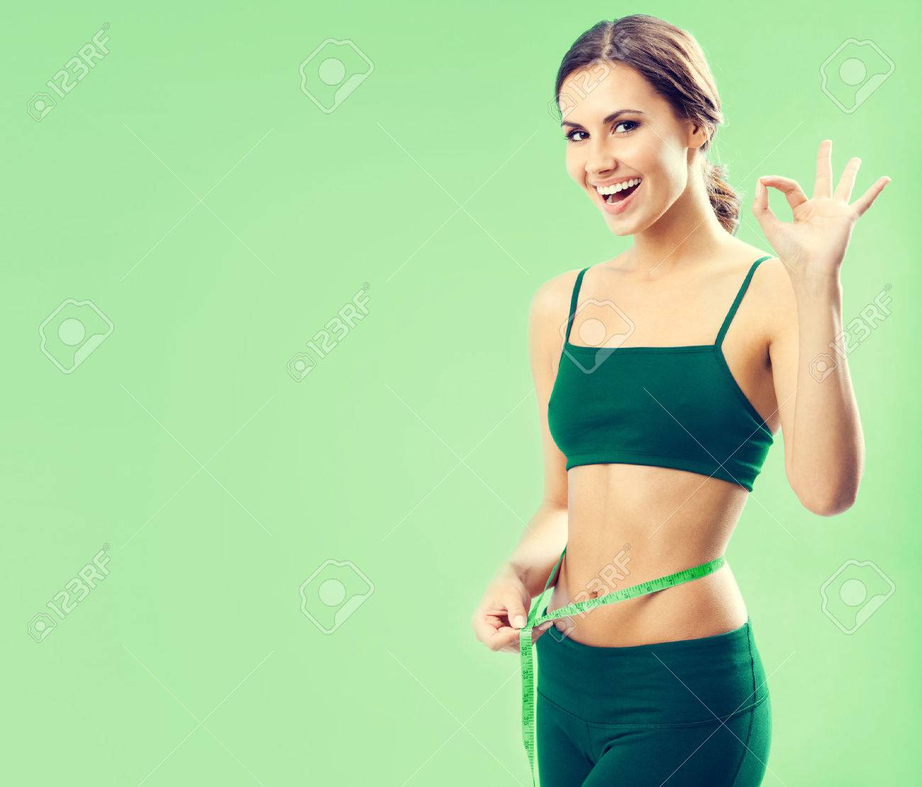 Portrait of smiling young lovely woman in fitness wear with tape, showing okay gesture, over green background, with blank copyspace area for text or slogan Banque d'images - 43738060