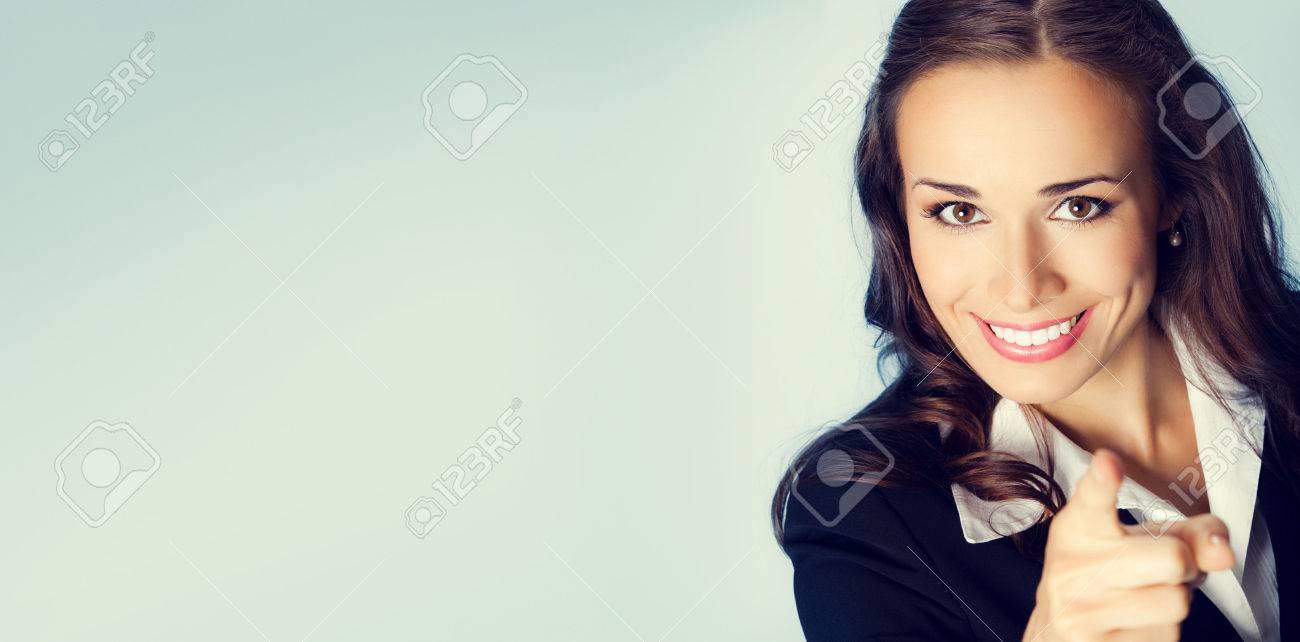 Portrait of young smiling brunette businesswoman pointing finger at viewer, with blank copyspace area for slogan or text message - 44407458