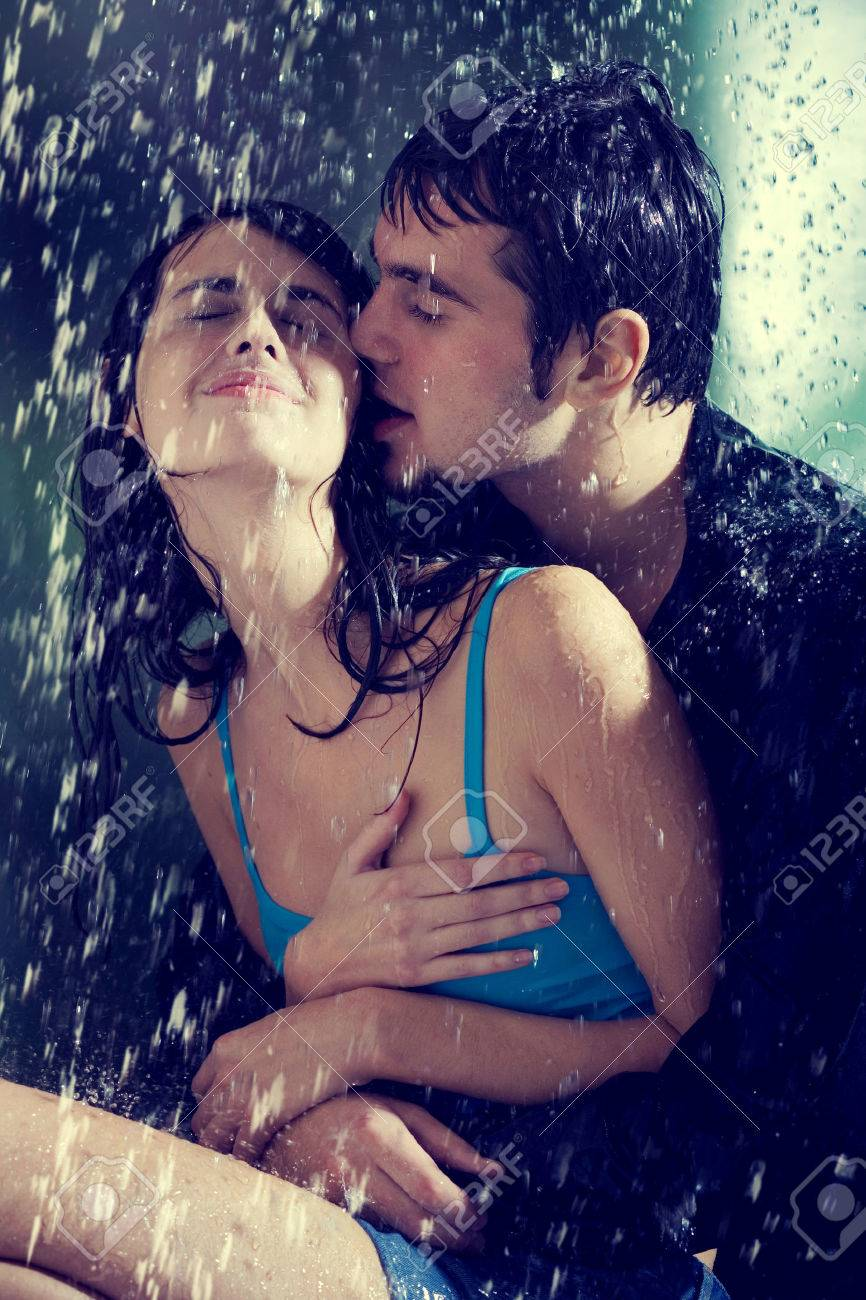 young couple hugging and kissing under a rain in passion stock