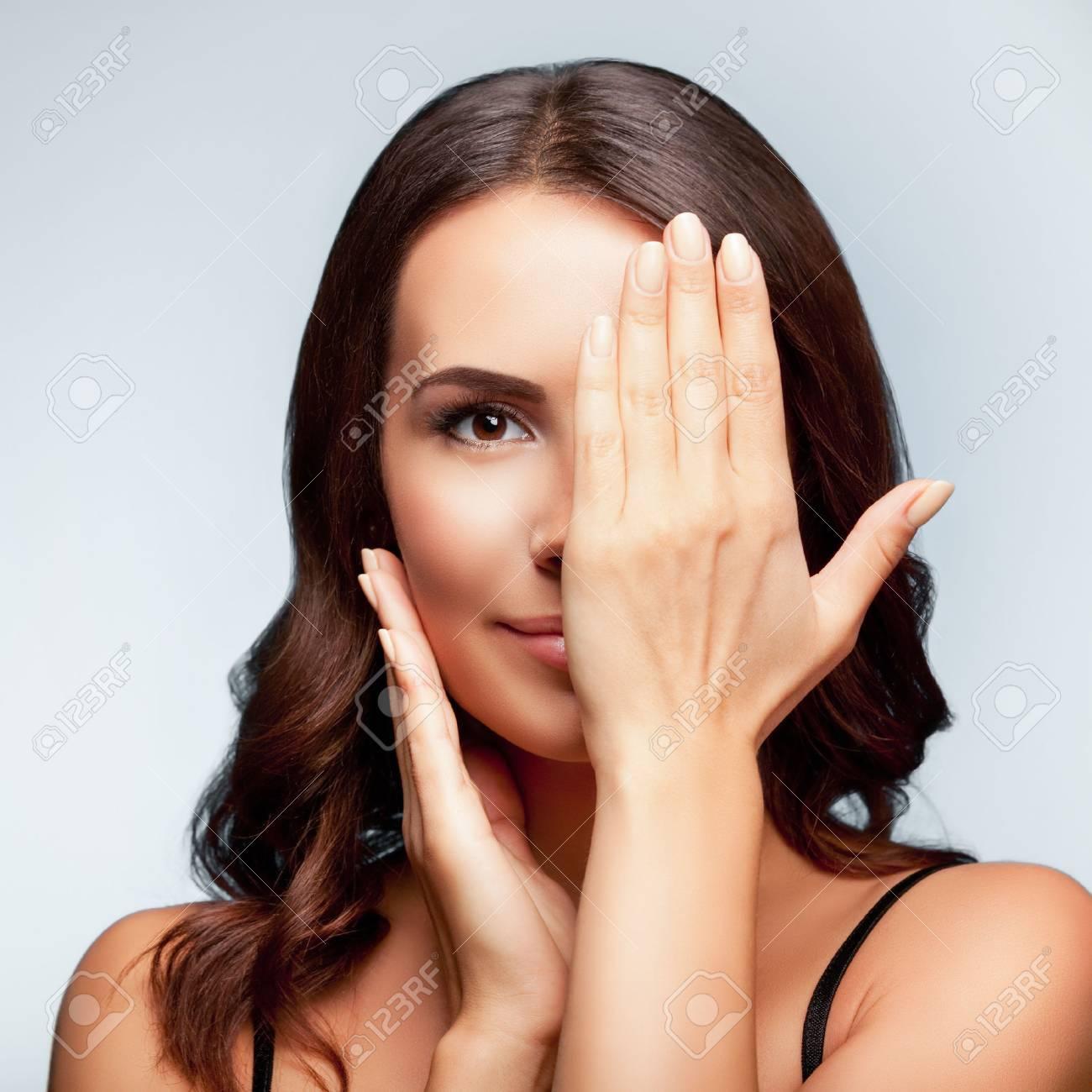 jeune femme souriante, l'?il, clossed à la main, couvrant une partie de son visage, sur fond gris clair, composition carré Banque d'images - 44672750