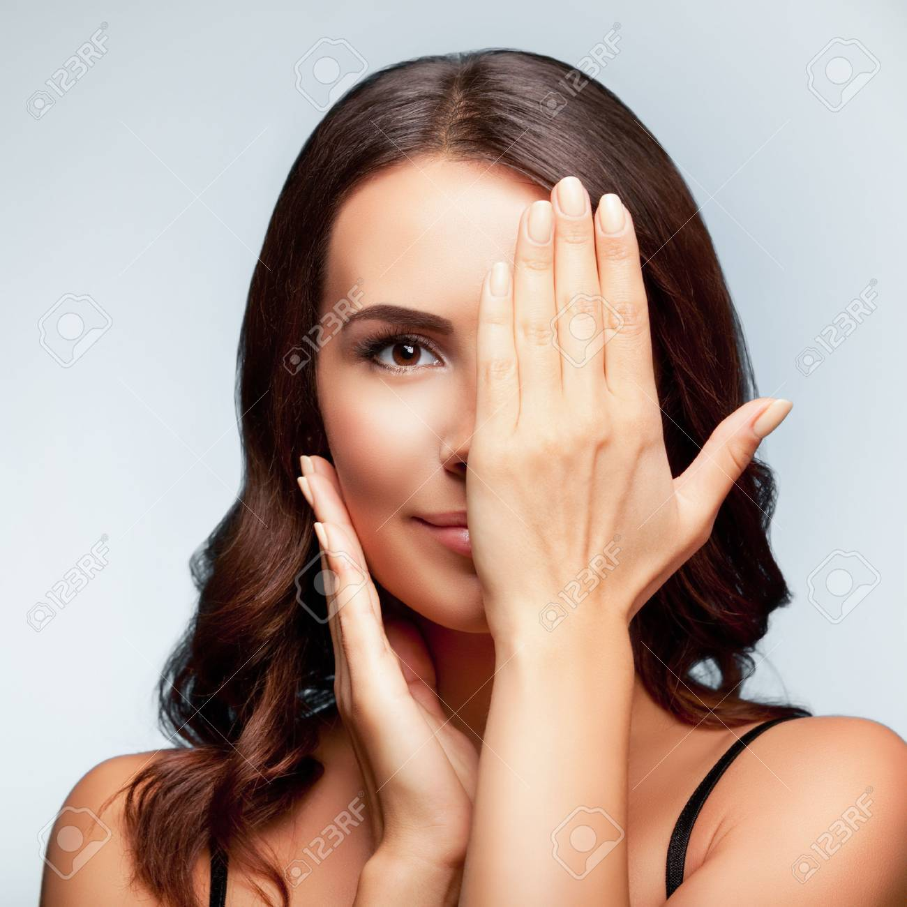 smiling young woman, with eye, clossed by hand, covering part of her face, over bright grey background, square composition Banque d'images - 44672750