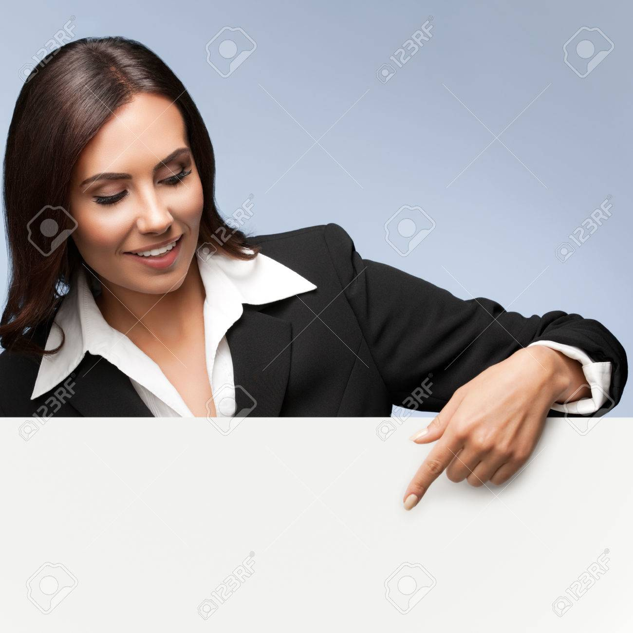 Portrait of happy smiling young businesswoman in black suit, showing blank signboard with blank copyspace area for slogan or text, over grey background - 51350129