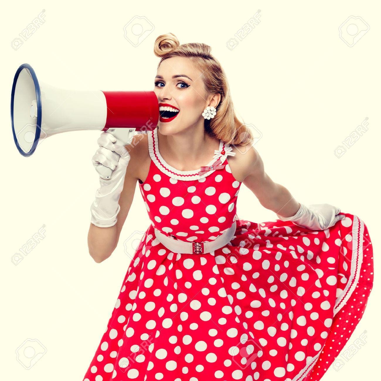 Portrait de la belle jeune femme heureuse tenant un mégaphone, habillé dans le style robe rouge de pin-up à pois et des gants blancs. modèle blond caucasien posant dans la mode rétro et vintage tournage concept de studio. Banque d'images - 52082943