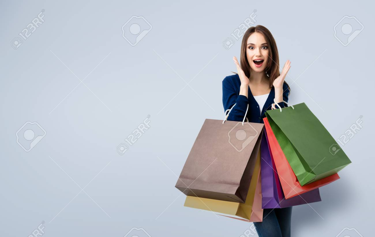 Very happy beautiful young woman in casual clothing with shopping bags, with copyspace area for text or slogan - 59131382