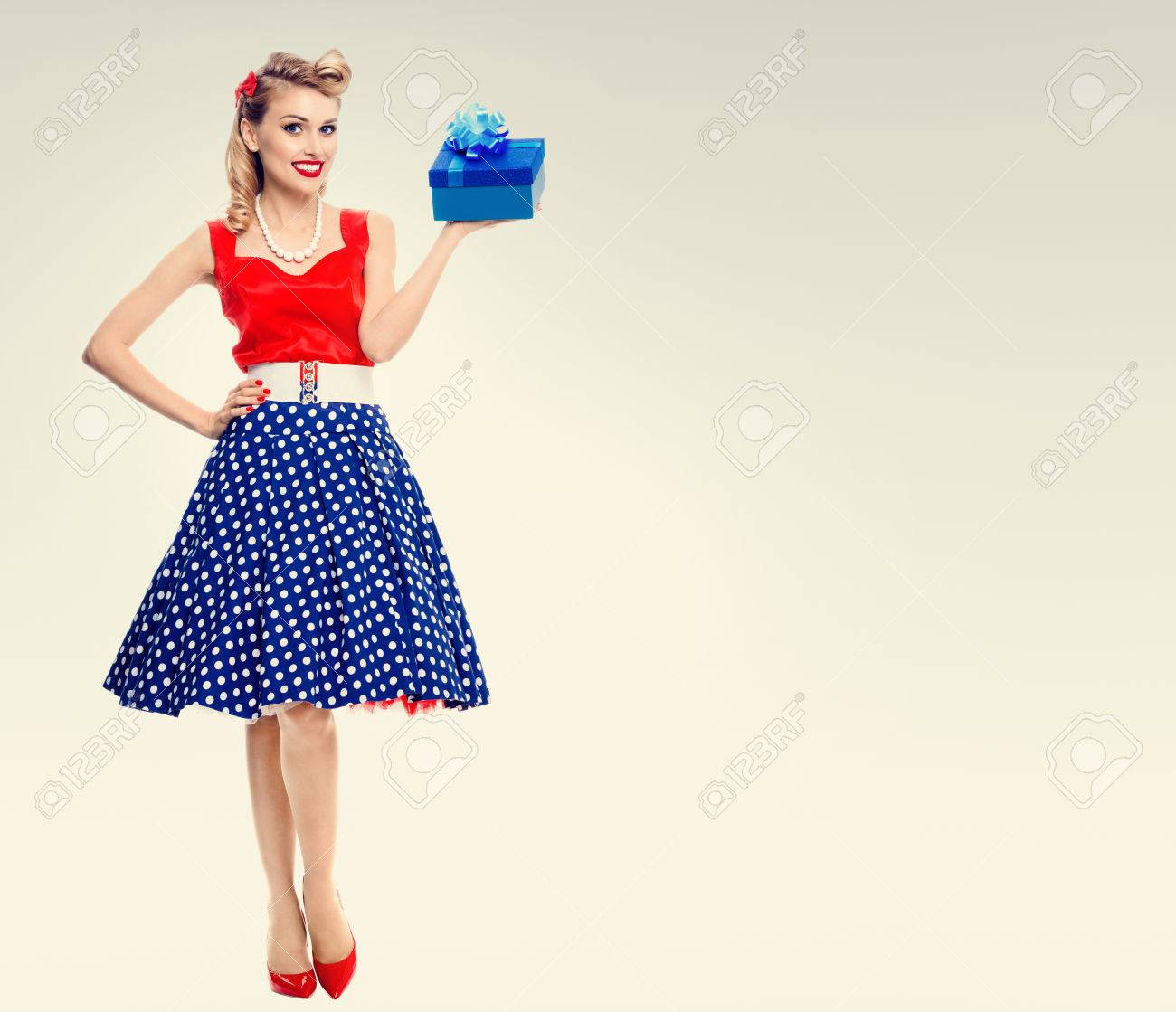 Full body portrait of smiling woman dressed in pin up style dress..