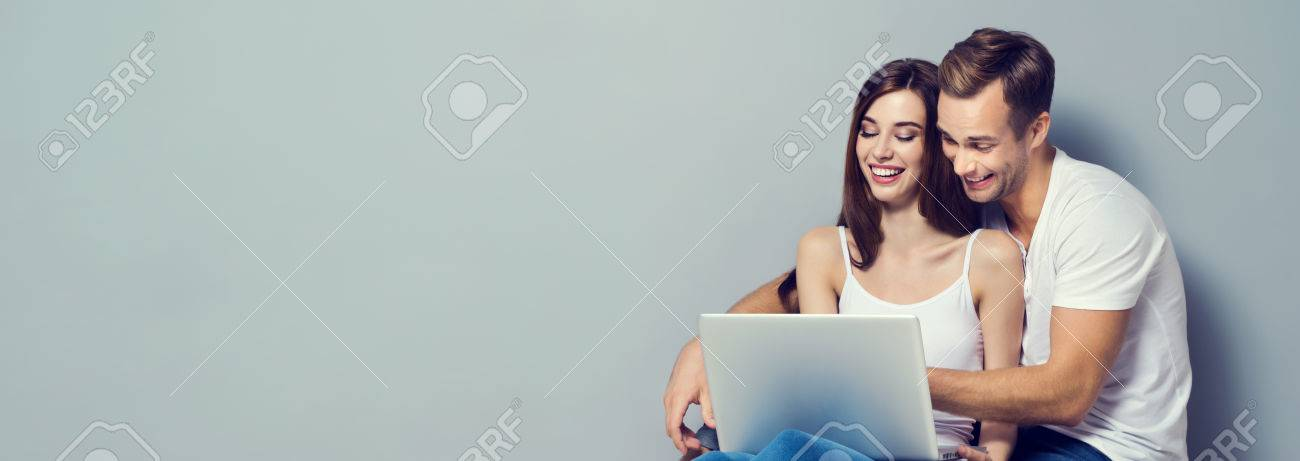 Beautiful young happy smiling couple using laptop, sitting on floor, close to each other. Caucasian models - internet, technology, family, love, relationship, happiness, concept shot. Horizontal banner composition . Copyspace for slogan or text message. Banque d'images - 69177098