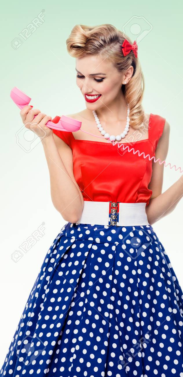Funny portrait of beautiful woman with phone dressed in pin up..