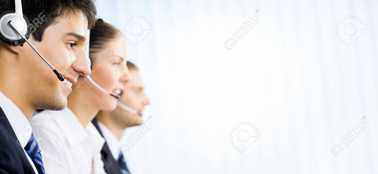 Three happy customer support phone operators at office, with copyspace area for text, advertisiment or slogan. Consulting and assistance service call center. - 73562547