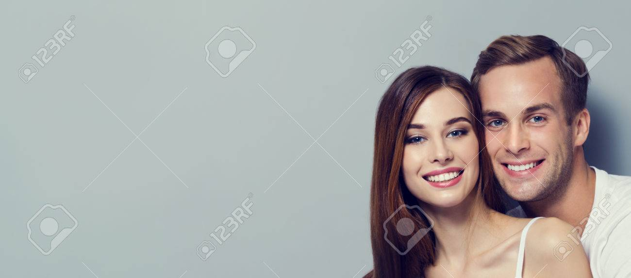 Portrait of young couple, looking at you. Caucasian models - love, relationship, dating, happy lovers, concept, against grey, with copyspace for slogan or text message. Horizontal banner composition. - 75499568