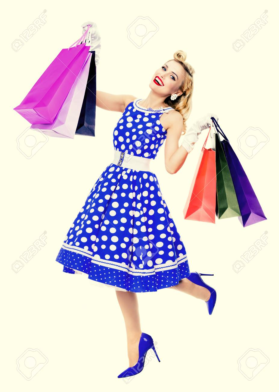 Full body portrait of woman in pin up style blue dress in polka..