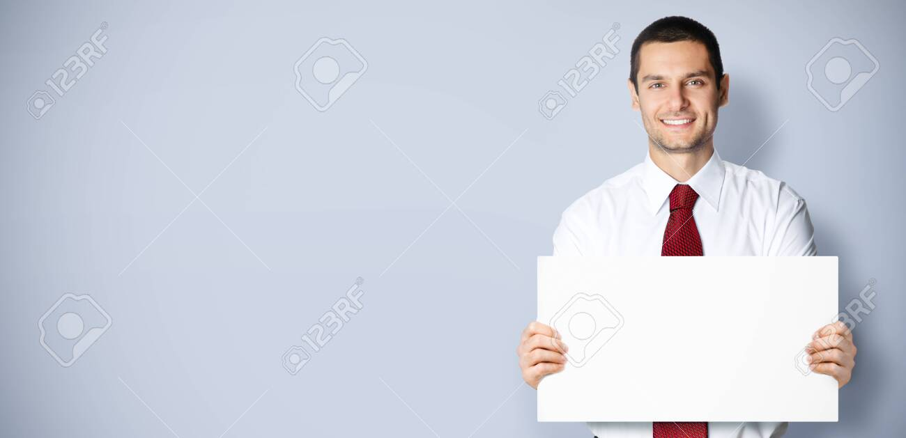 Business concept photo of businessman showing blank signboard, with empty copy space place for some text, advertising or slogan, over grey background - 121273922