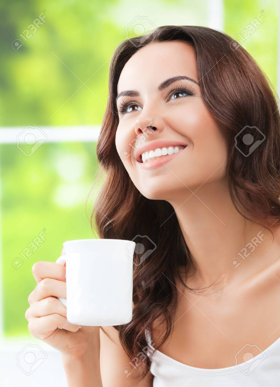 Portrait of young happy girl drinking coffee or tea, at home - 122465048