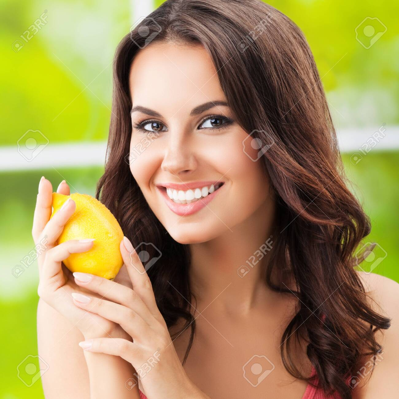 Young happy smiling beautiful woman with lemon, outdoors - 126403231