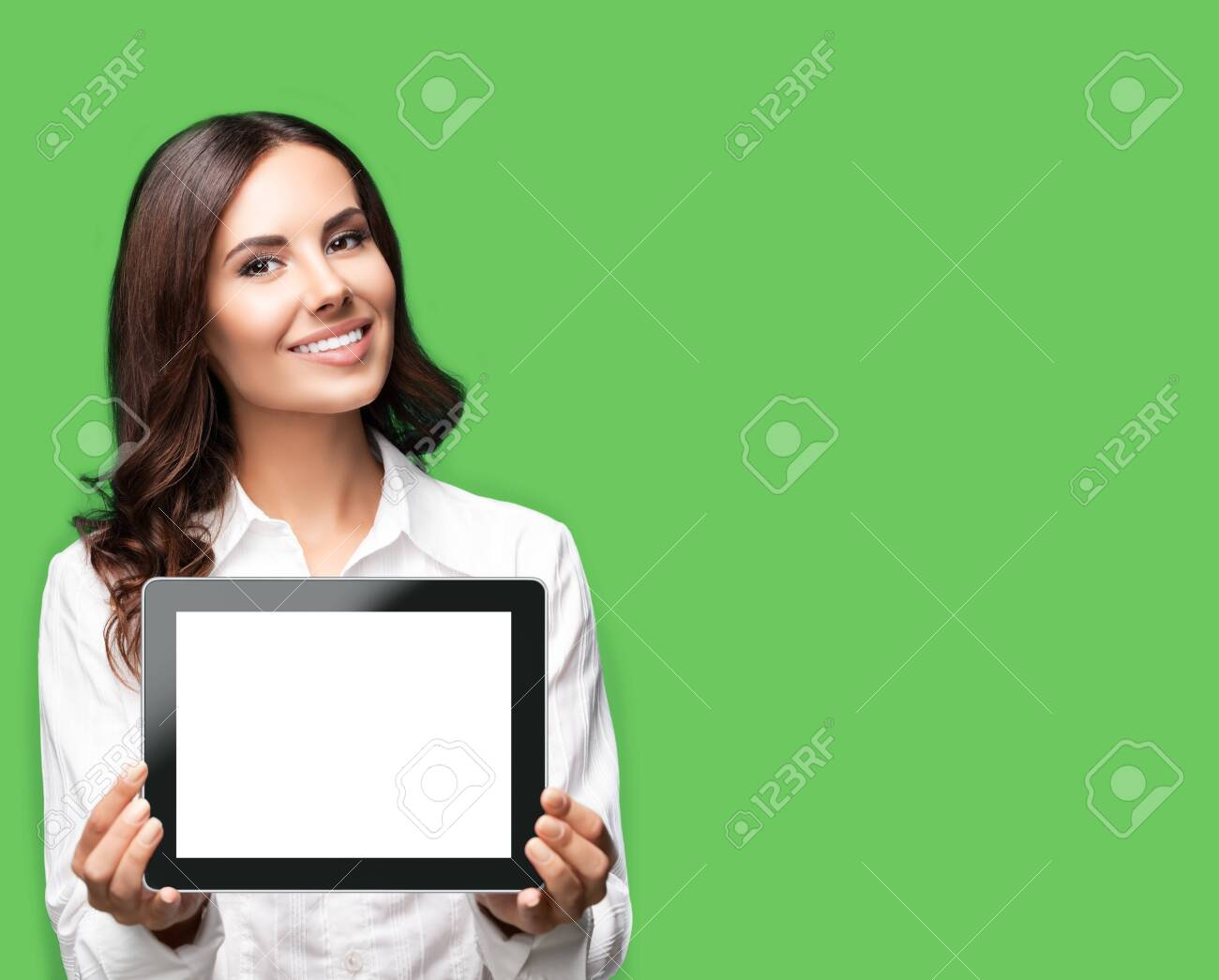 Cheerful beautiful brunette confident businesswoman showing blank no-name tablet pc monitor, over green color background, with copy space area for some text. Success in business concept. - 142455094