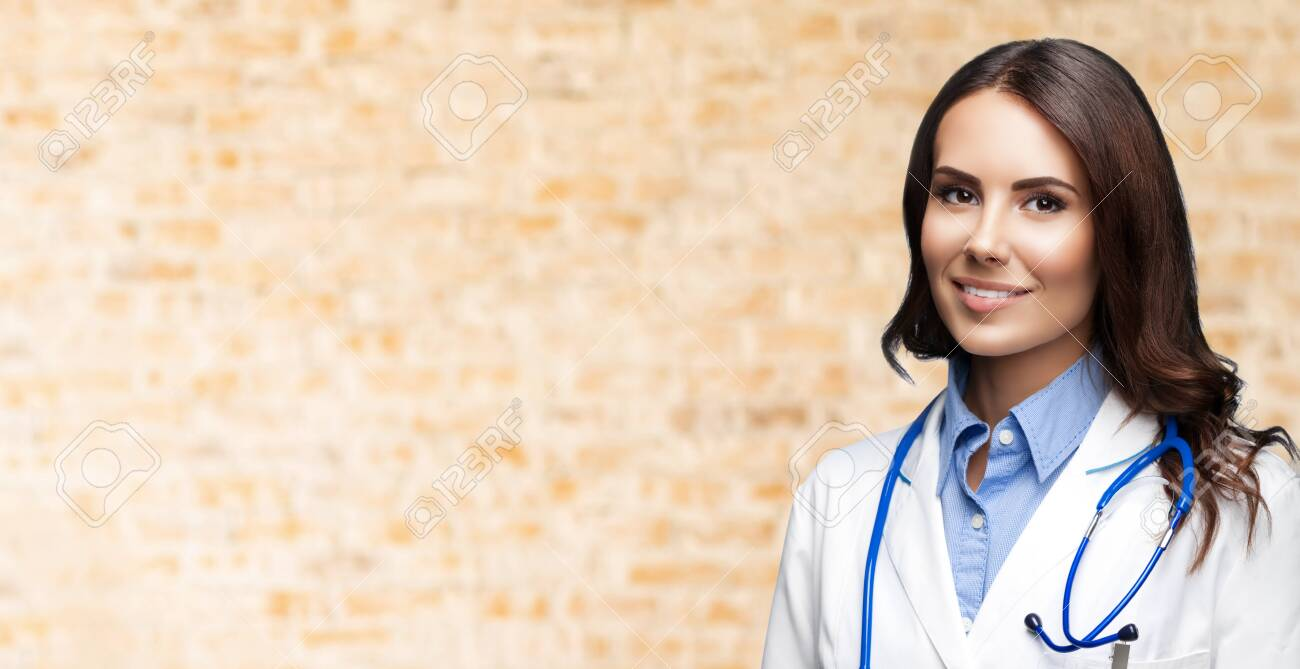Portrait picture of happy smiling female doctor in white uniform coat and stethoscope, over loft style wall background. Healthcare, medical, medicine specialist - concept. Copy space. - 146299334