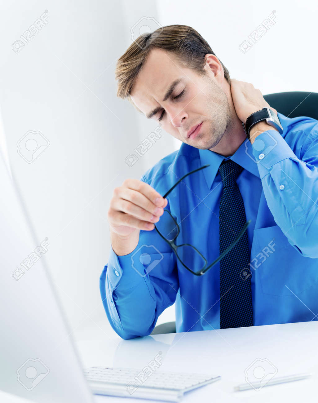 Image of frustrated, exhausted or tired business man in confident blue shirt, with glasses, touching neck. Businessman with computer at office. - 171475872