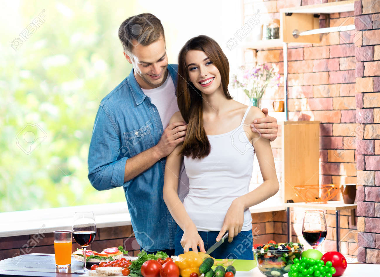 Image of happy amazed amorous couple cooking together at domestic kitchen with vegetarian healthy fresh food. Young family and healthy diet eating concept. - 171473217