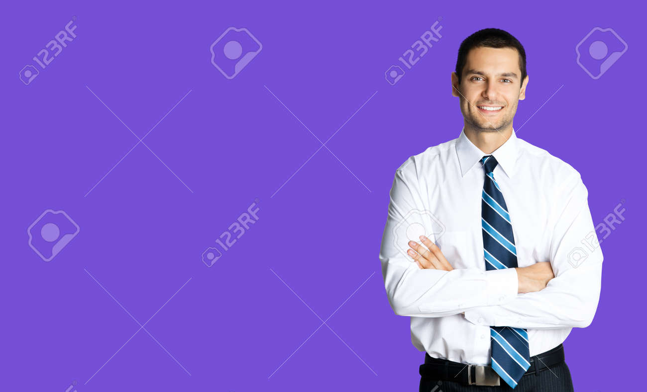 Portrait of happy smiling young brunette businessman in white shirt and blue tie, standing in crossed arms pose, isolated over violet purple colour background with copy space. Confident business man. - 171559468
