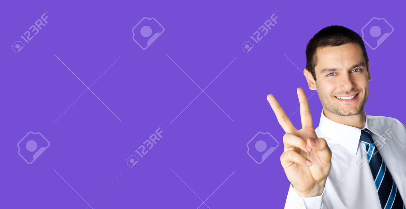 Businessman in white confident shirt and tie showing two fingers or victory gesture, over violet purple color background. Happy smiling gesturing brunette man at studio. Business ad concept. - 171559974