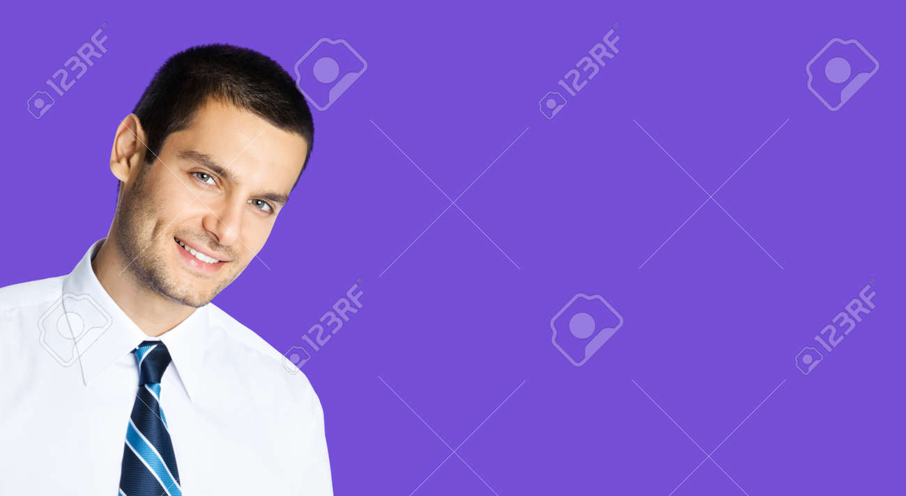 Portrait of happy smiling young brunette businessman in white shirt and blue tie, isolated over violet purple colour background with copy space area. Confident business man at studio image. - 171514954