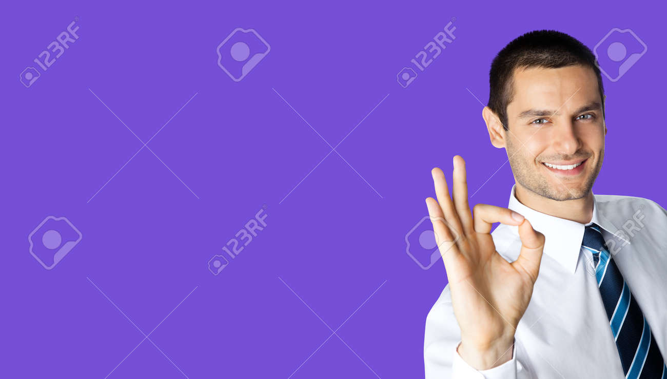Portrait of smiling businessman in white shirt and tie, showing thumb up like hand sign gesture, isolated over violet purple colour background. Happy confident man gesturing. Business success concept. - 171559976