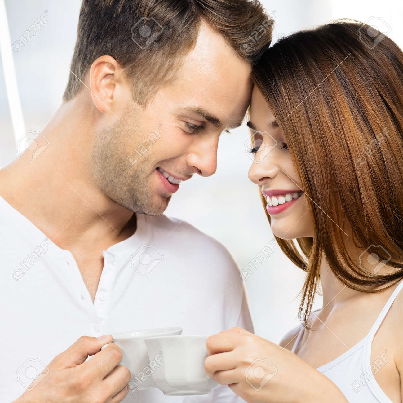 Image of smiling happy amazed couple with cups of some drinks at home. Portrait of standing close and looking at each other models in love family concept. Man and woman posing together. Square. - 171533130