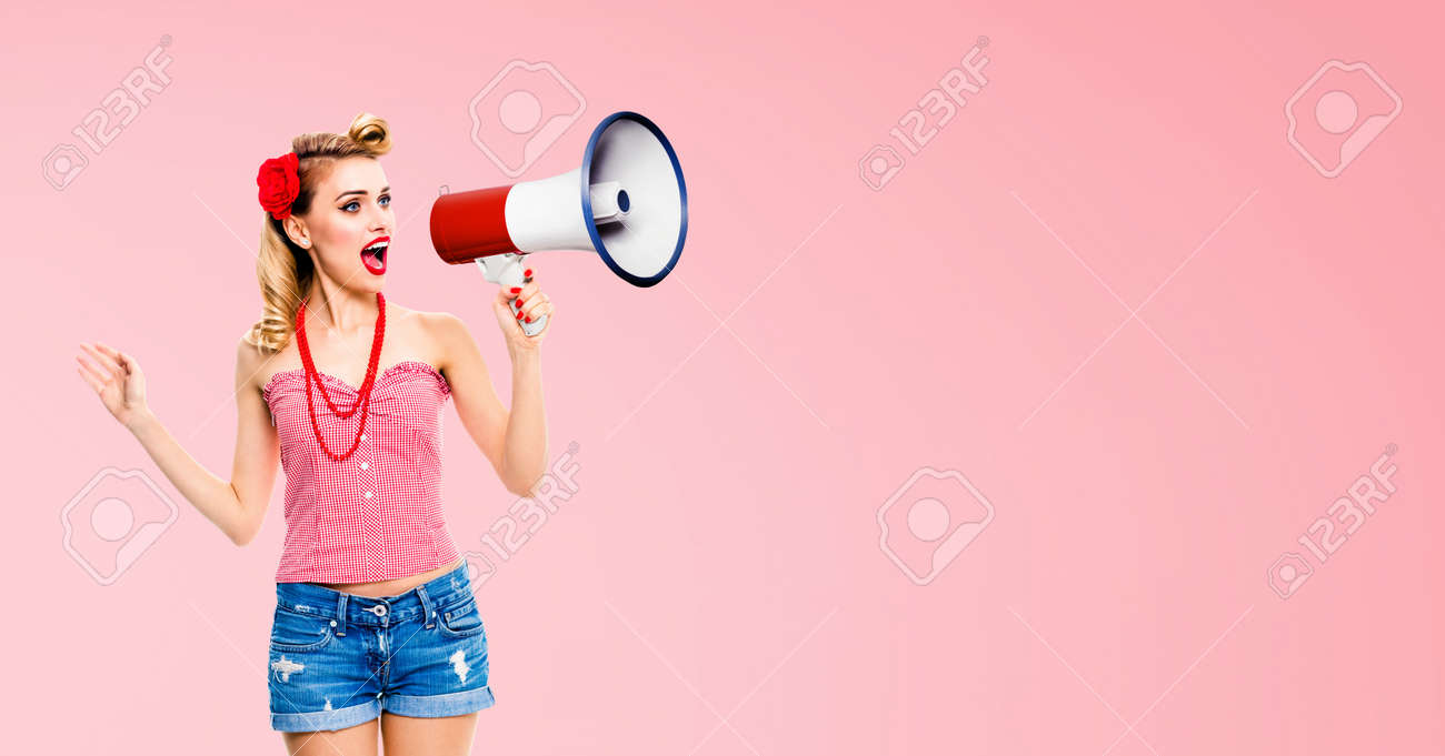 Image of blond haired woman holding megaphone, shout something. Girl in red pin up style, isolated over rose pink colour back. Female model in retro vintage studio concept. - 171535821