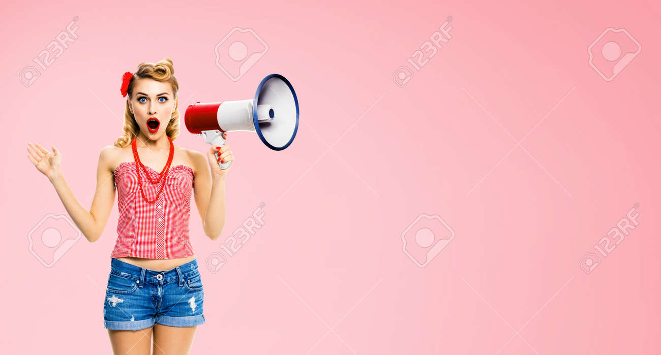 Image of beauty blond haired woman holding megaphone, shout something. Girl in red pin up style clothing, isolated over rose pink colour back. Female model in retro vintage concept. - 171535551