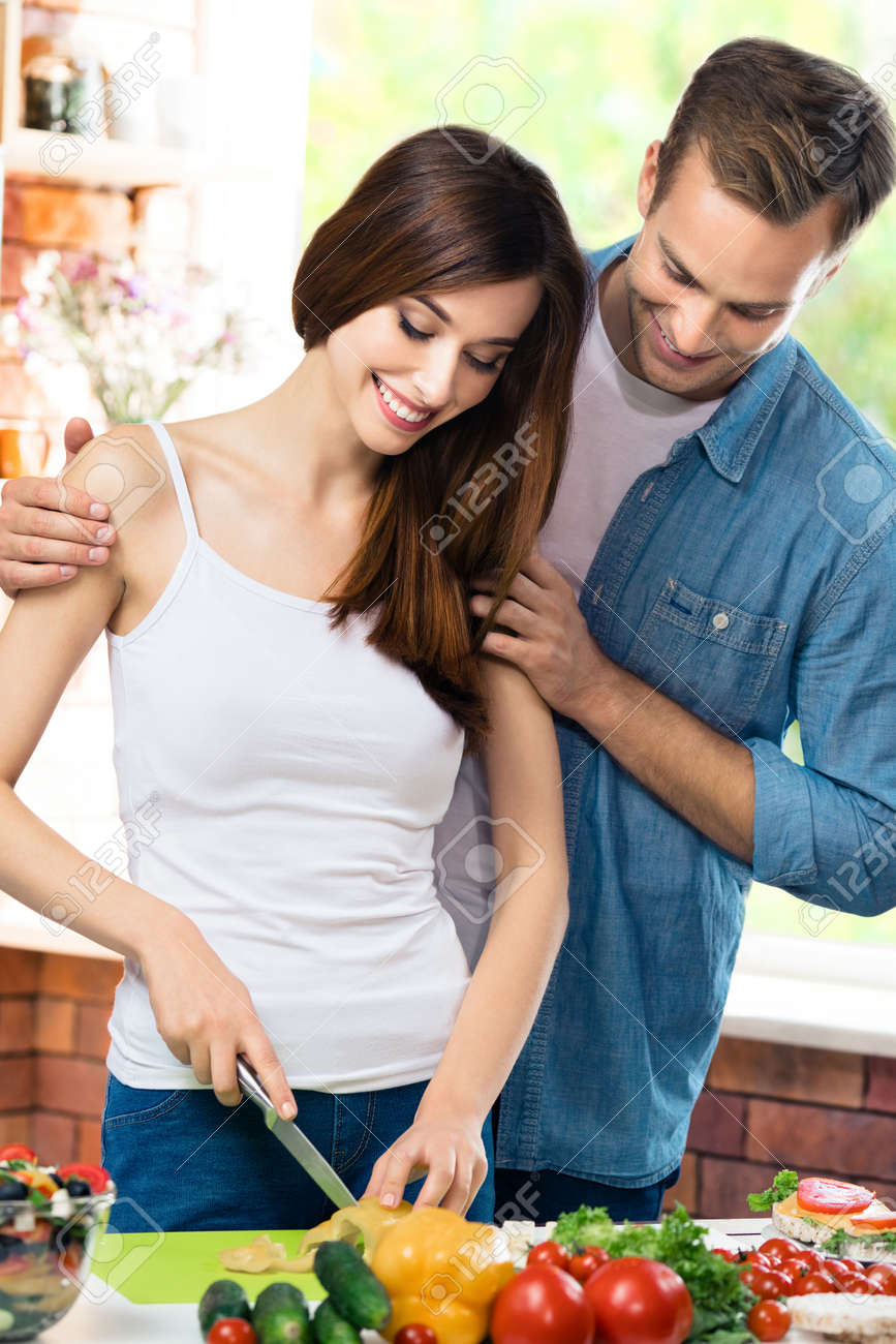Image of happy amazed couple cooking together at kitchen with vegetarian healthy fresh food. Love, romantic, young family and healthy dieting eating concept. Man and woman. - 171576236