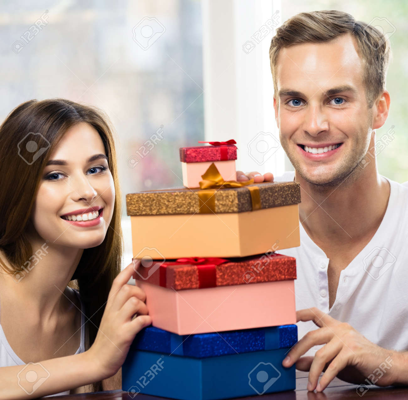 Square image of happy excited smiling couple with gifts boxes, at home. Shopping, holiday sales, love, relationship concept - young man and woman, indoors. - 171576282
