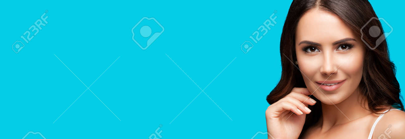 Portrait of smiling beautiful woman in white casual tank top, over aqua blue green background. Brunette girl at studio beauty fashion concept. Wide horizontal banner composition. - 171582170