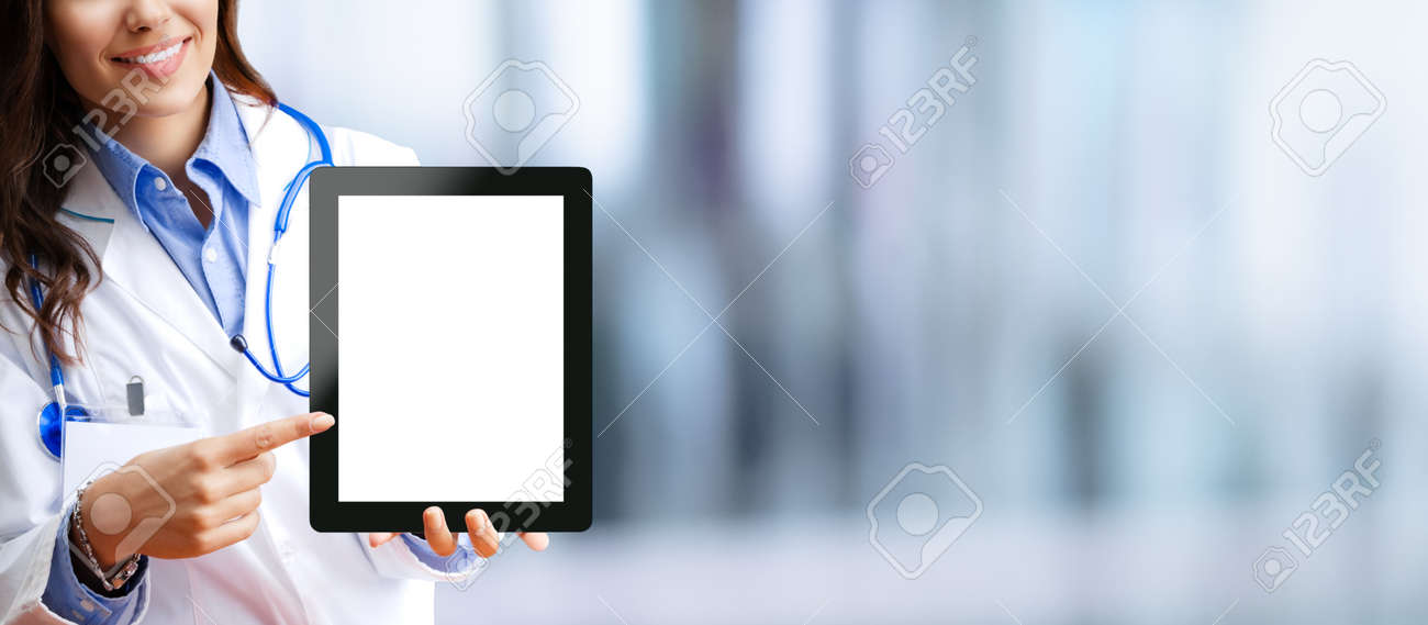 Close up of happy smiling female doctor showing tablet pc touchpad with blank copy space area for some text, over blurred modern office background. Medical help call center concept. - 171588156