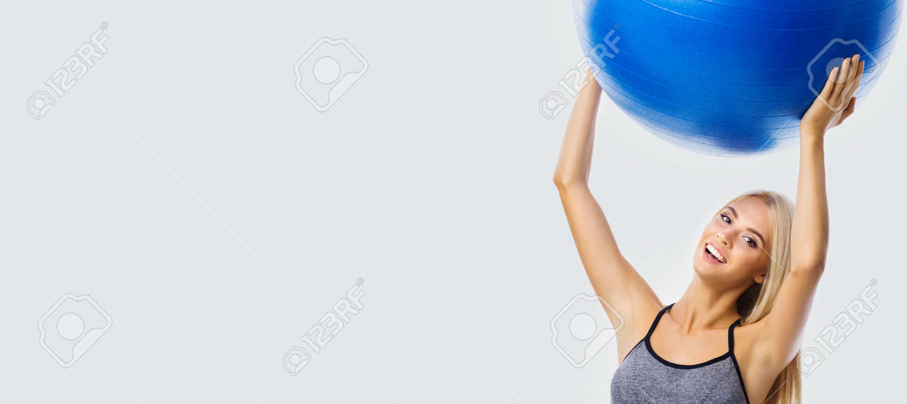 Beautiful smiling woman in sportswear holding fitness blue ball, isolated over grey color background. Blond girl in fit exercising studio concept. Wide banner composition. - 171779203